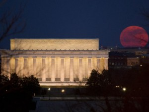 The full moon is seen as it rises near the Lincoln Memorial
